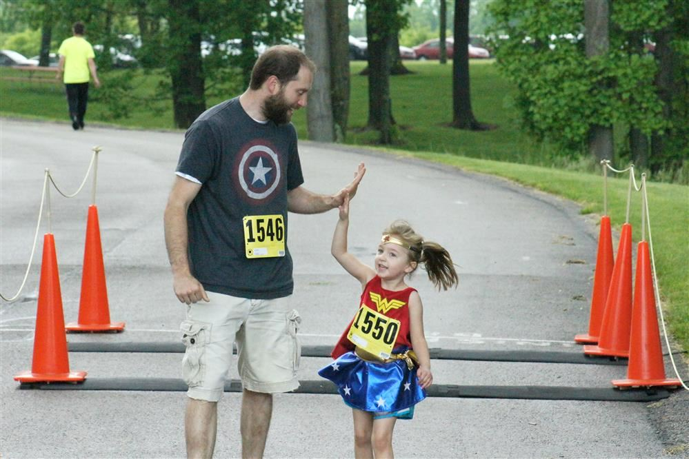 A father, left, high-fives his daughter, right, as they cross the finish line of the Sunrise Super Hero 5K race.