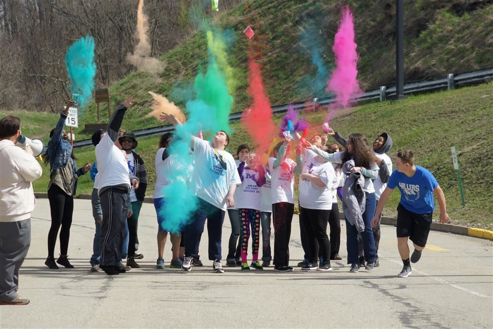 Runners at the starting line throw colorful packets into the air at the start of the Mon Valley Dye Hard Challenge race.